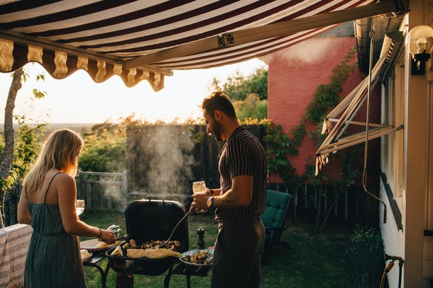 A couple barbecues in the backyard with drinks in their hands.