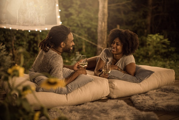 A couple relaxes in the backyard with pillows, drinks, and an outdoor movie screen.