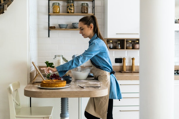 A young woman bakes a fruity cake in her kitchen while wearing an apron and scrolling on her tablet.