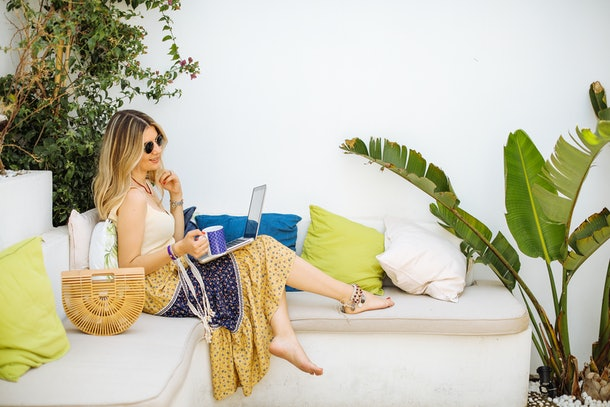 A young woman sits on a luxe patio with her feet up on the cushion, and her laptop and a cup of coffee in her hands.