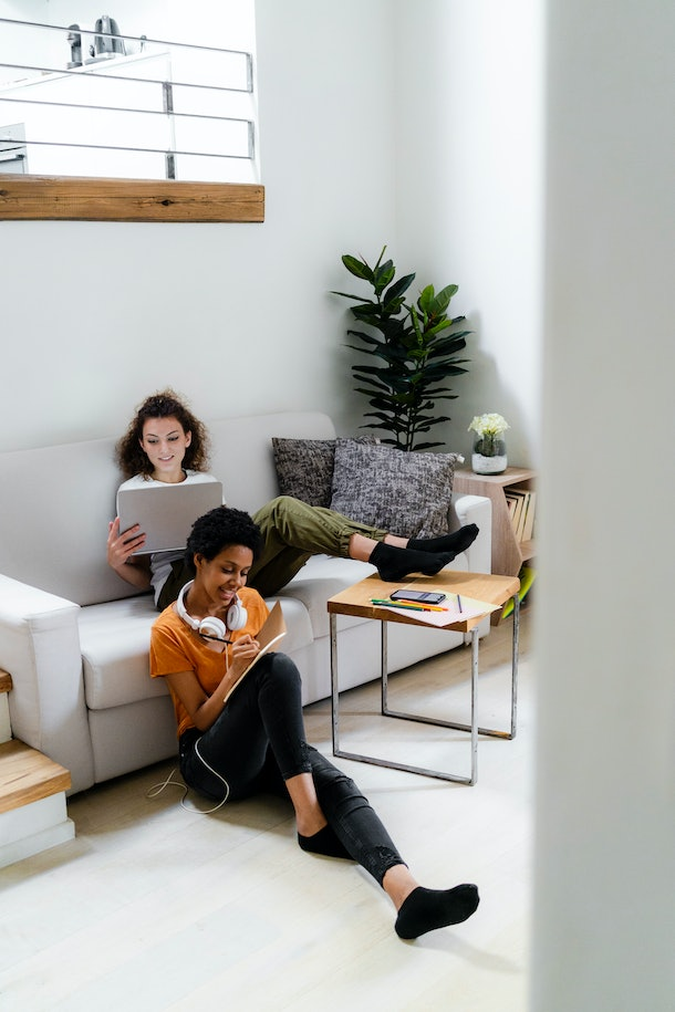 Two young women relax in their stylish and minimalistic living room, and take notes on a virtual class.