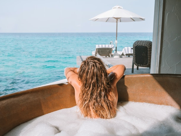 A young woman with blonde hair looks out at the ocean while in a bubble bath on vacation.