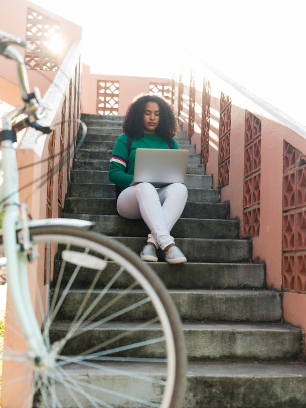 A young Black woman sits on an outdoor staircase and types on her laptop.