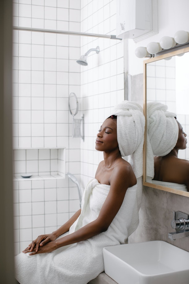 A young Black woman relaxes in her bathroom after taking a bubble bath.