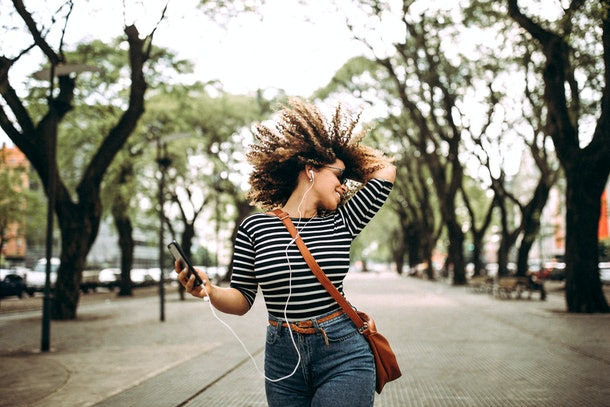 A happy woman dancing outside with her phone.