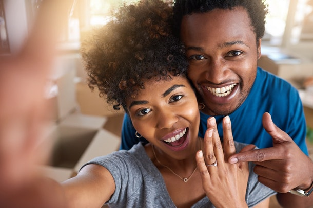 A happy couple takes a selfie showing off their engagement ring.