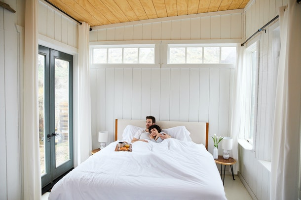 A young couple snuggles in bed with a breakfast tray nearby while on vacation.