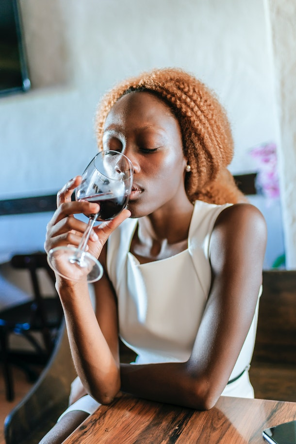 A young Black woman sits at a table and sips on a glass of red wine.