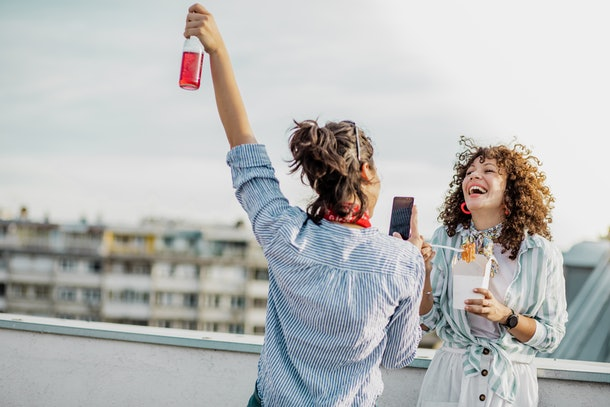 A friend takes a video of her friend eating noodles on their rooftop.