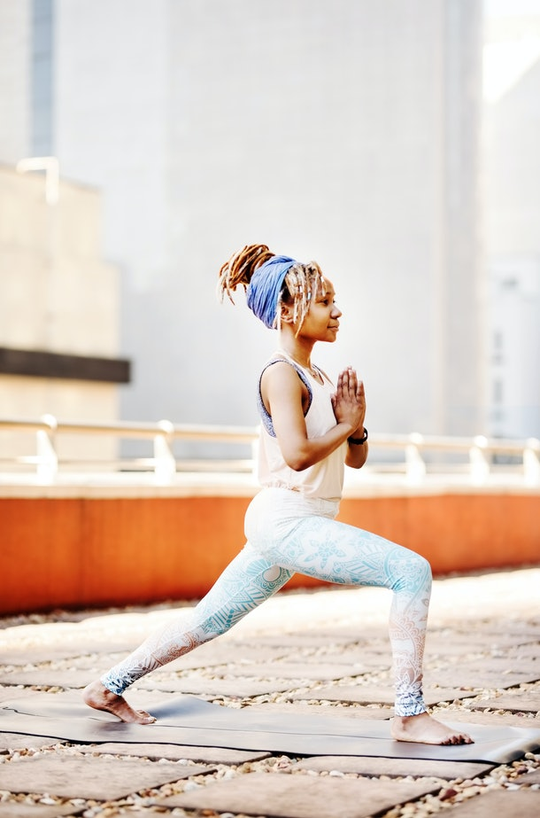 A young Black woman does yoga on the rooftop of her apartment building in the city.