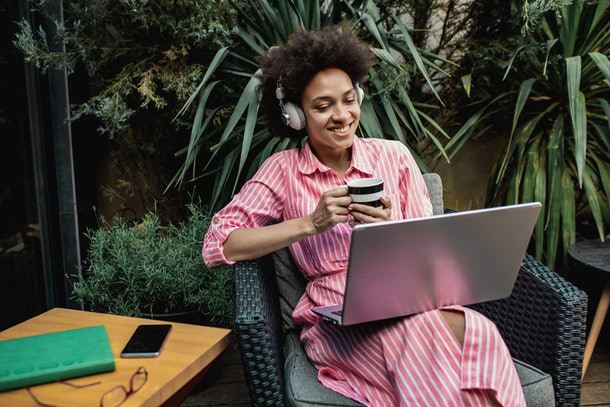 A young Black woman sits with her laptop on her back patio that's surrounded with plants and palm leaves.