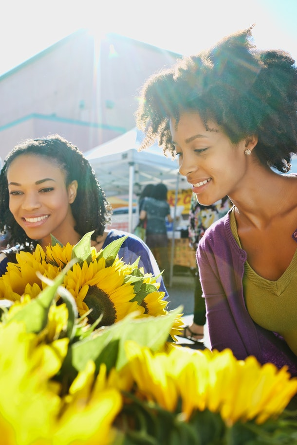 Two young Black women shop for sunflowers at the farmer's market in their city.