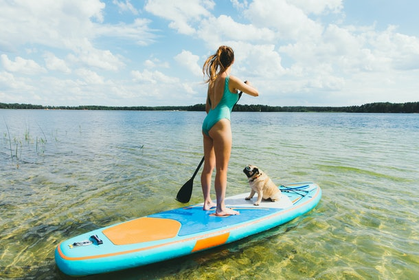 A young woman paddleboards on a lake behind her house with her pug.
