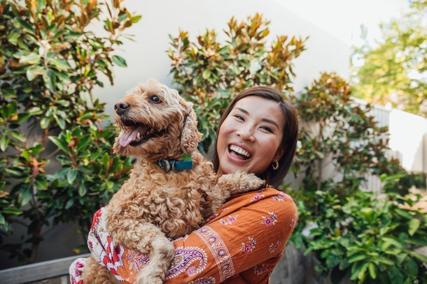 A young Asian woman holds her golden doodle and smiles brightly while standing amongst the plants in her backyard.