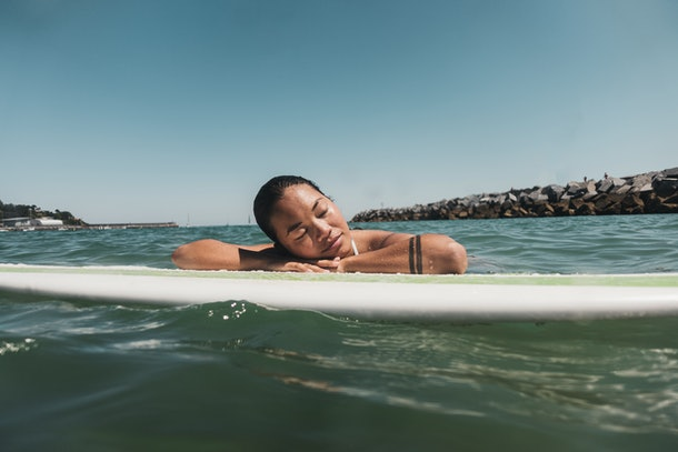 A young Asian woman relaxes on a surfboard in the middle of an ocean on a summer day.
