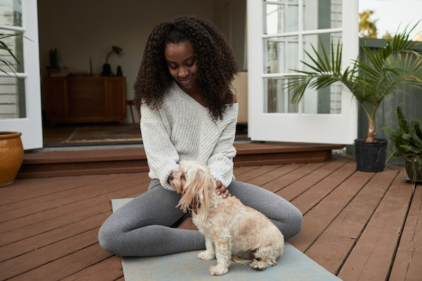 A young Black woman sits on a yoga mat on her deck and pets her pup.