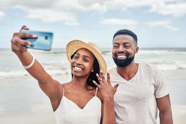 A young Black couple poses for a selfie after getting engaged on the beach.