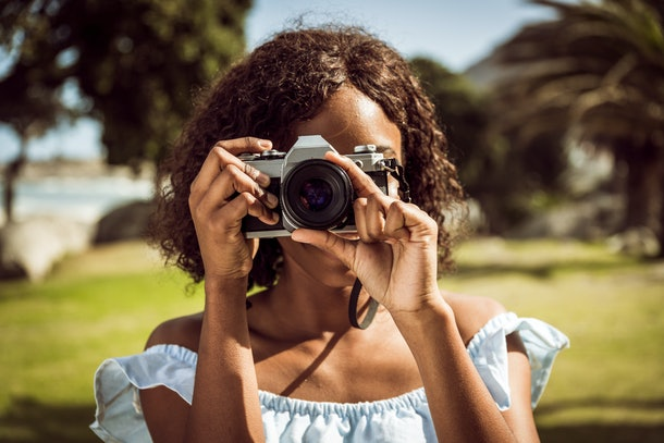 A young Black woman holds up a film camera and uses the zoom ring on a summer day.