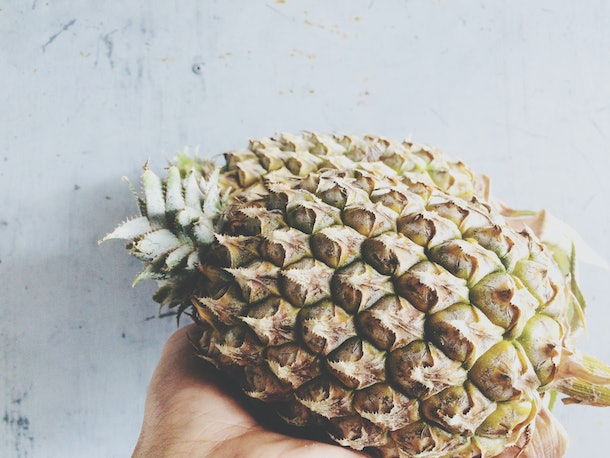 A young woman holds a pineapple in her hand against a white countertop.