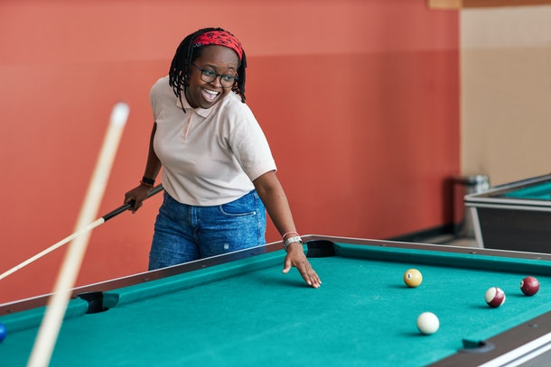 A young Black woman laughs while playing pool in a college collab house.