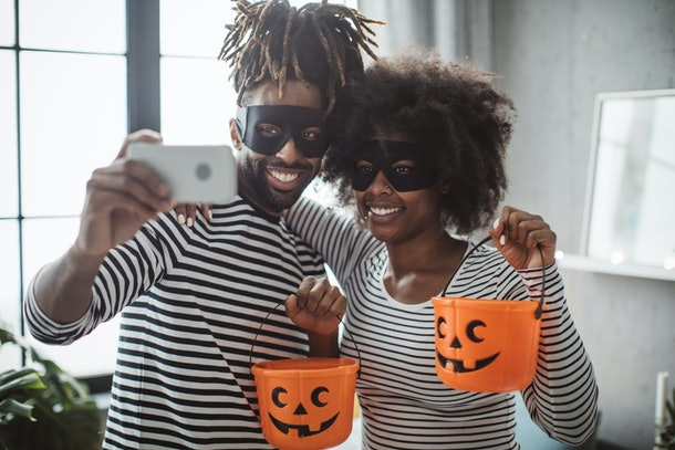 A couple dressed up for Halloween with pumpkin buckets, pose for a selfie on their phone.