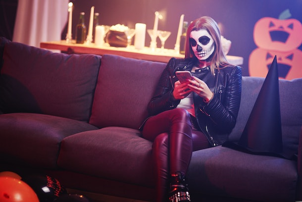 A woman dressed as a skeleton looks at her phone while sitting on her couch at home.