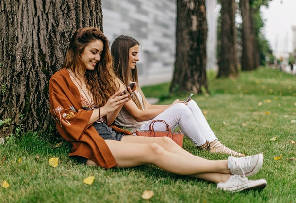 Two women sit in the grass by a tree while texting.
