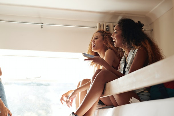 Two women laugh while sitting on a top bunk in a bright dorm room.