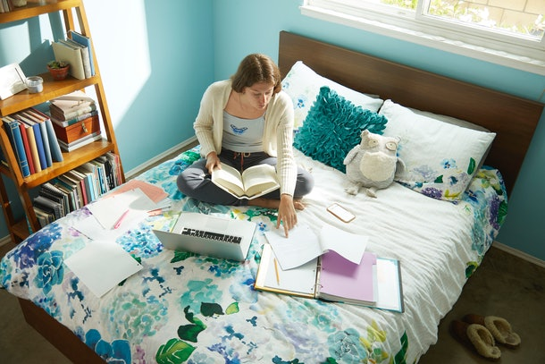 A woman studies on her bed in her college dorm room.