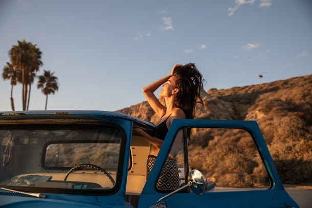 A young Asian woman runs her fingers through her hair while posing with a vintage car at sunset at the beach.