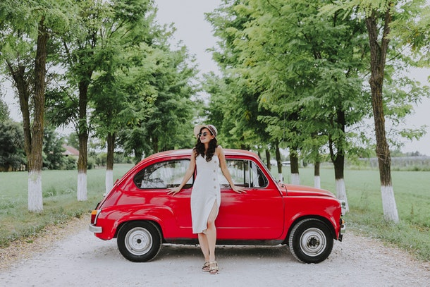 A young woman in a white dress poses against a red, classic car that's parked on a dirt road.