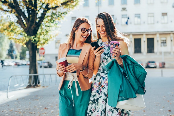 Two trendy women in chic clothes hold to-go coffee cups and laugh while looking at one of their phones.