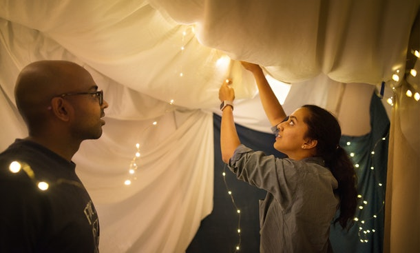 A young couple sets up a fort in their living room with sheets and string lights.