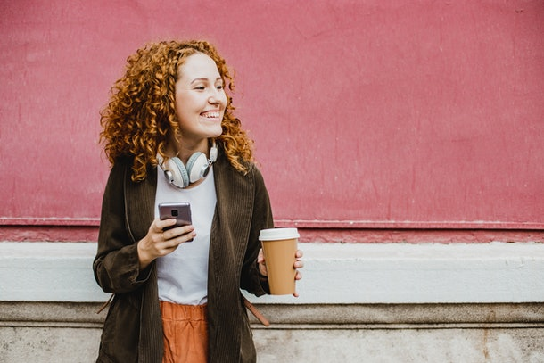 A young woman with red hair smiles while holding a coffee and her phone, and standing in front of a pink wall.