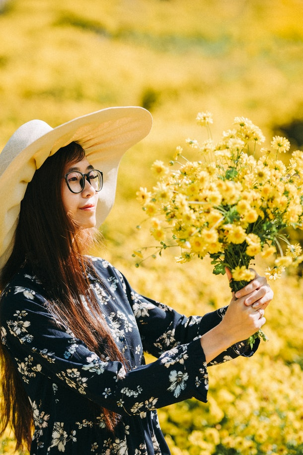 A young Asian woman smiles at a bouquet of freshly-picked yellow flowers while standing in a field.