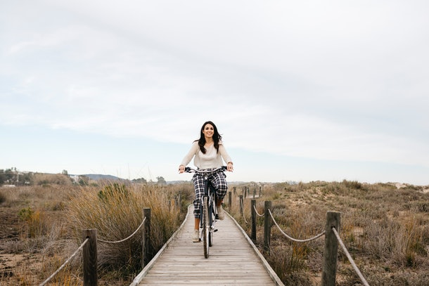 A young woman bikes down a tiny boardwalk near the beach.