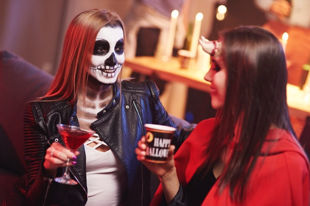 A couple dressed in Halloween costumes, sit on the couch at a party with cocktails in hand.