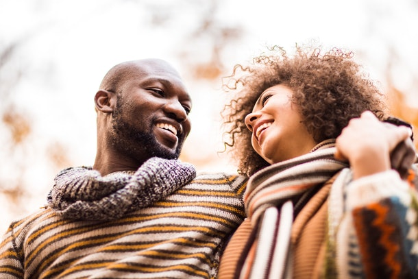 A young Black couple poses for a professional photo while wearing cozy attire, and standing near fall trees.