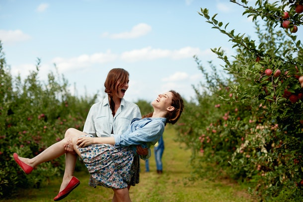 Two sisters dressed in button-down shirts and skirts laugh while at an apple orchard.
