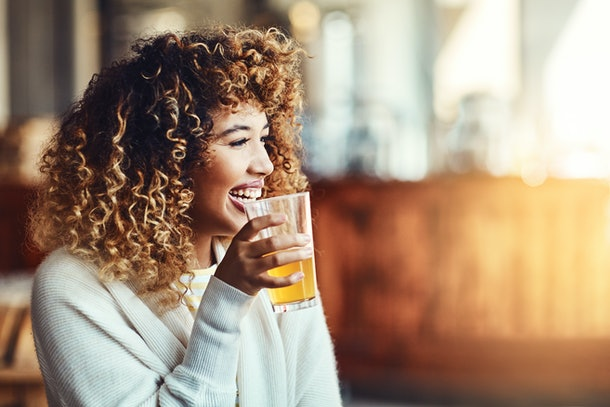 A happy woman in a sweater laughs while holding her cup of beer.