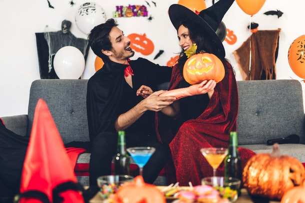 A couple dressed up for Halloween embraces on the couch with Halloween decor all around.