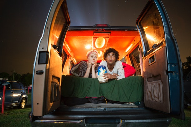 A young couple sits in the trunk of their car and watches a movie at a drive-in.