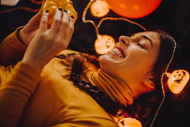 A women smiles while surrounded by pumpkin decorations for Halloween.