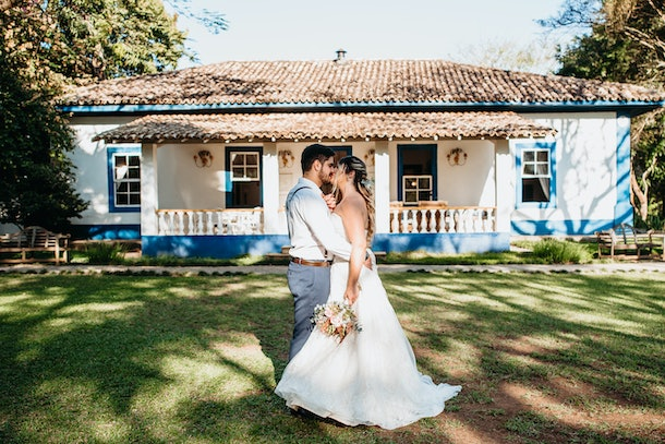 A young couple kisses in the backyard of their beach-like home after getting married.