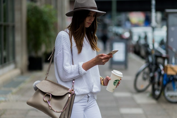 A woman in a felt hat, white sweater, and white jeans holds her Starbucks cup while texting on a city sidewalk.