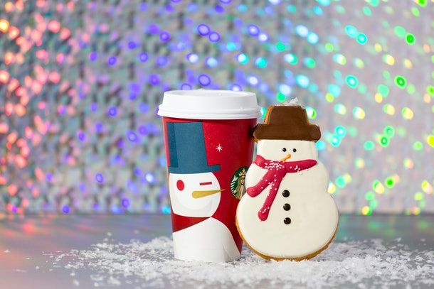 A holiday Starbucks cup is placed on fake snow with a snowman cookie next to it.