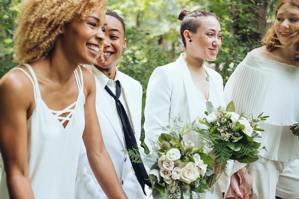 A group of four women hang out at a backyard wedding.