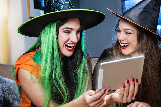 Friends dressed like witches on Halloween look at a tablet.