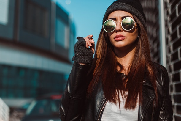 A trendy brunette woman dressed in a leather jacket, cork bottle sunglasses, and a beanie looks serious while walking down a sidewalk.