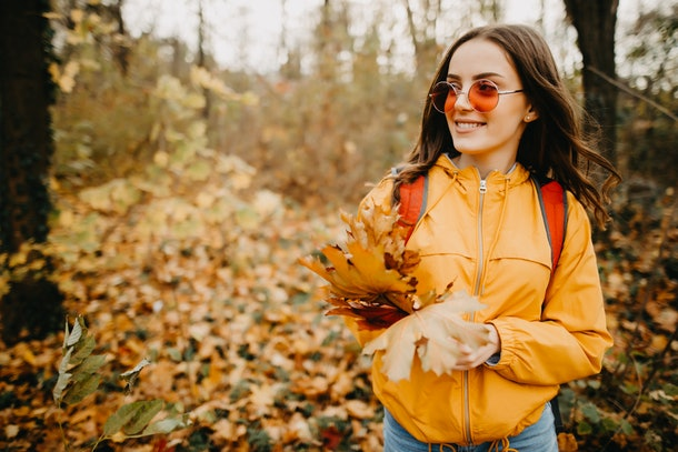 A young woman wears red, round sunglasses and a yellow jacket while having a photo shoot with leaves in the woods.